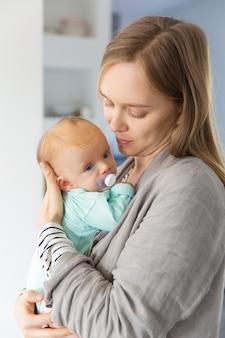 Nuova madre focalizzata che stringe a sé bambino con succhietto