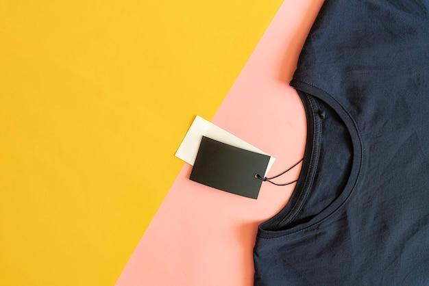Nuova maglietta casual con cartellino del prezzo di vendita con copia spazio isolato su sfondo rosa e giallo.