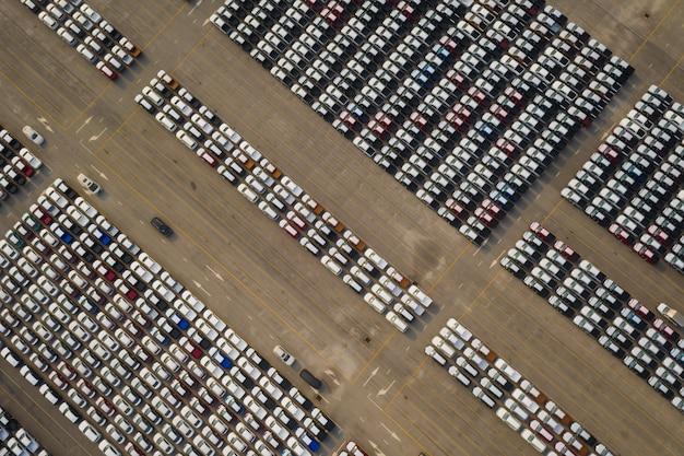 Nuove auto allineate nel parcheggio per la distribuzione internazionale per la vendita di affari da parte di grandi corgo container in mare aperto
