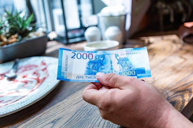 Nuove banconote russe denominate in 2000 rubli in una mano maschile, pagherà il conto in un ristorante