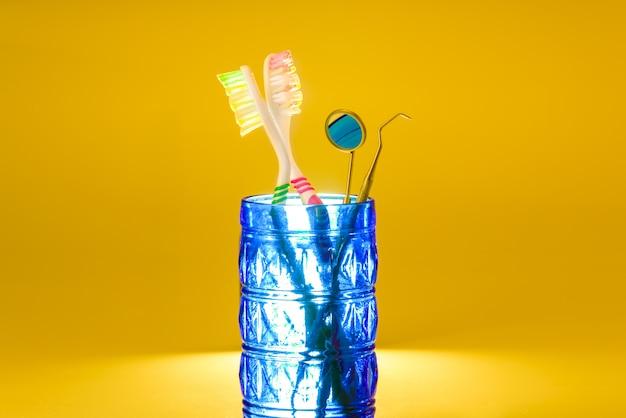 Nuovi spazzolini da denti in plastica all'interno di un bicchiere, isolato su arancio brillante