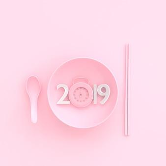 Nuovo anno 2019 concetto e orologio rosa pastello in ciotola con cucchiaio e bacchette.