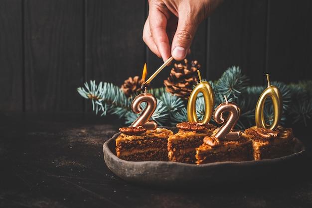 Nuovo anno 2020. torta festiva con candele sul tavolo scuro, copia spazio.