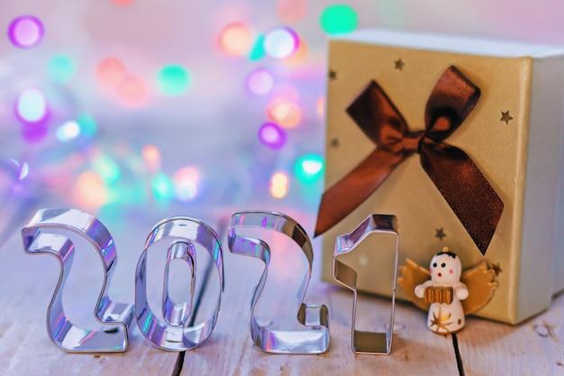 Nuovo anno 2021 e confezione regalo di natale con fiocco con luci colorate su fondo in legno o superficie, per mockup o design, fuoco selettivo