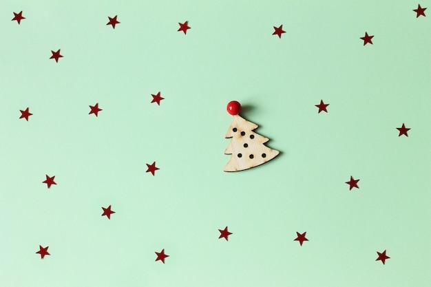 Nuovo anno piatto disteso da un giocattolo di legno, piccolo albero di natale su verde menta con coriandoli.
