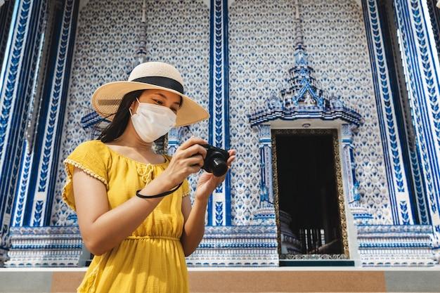 Nuovo concetto di viaggio normale, donna asiatica viaggiatore felice con maschera e macchina fotografica che fa un giro turistico in wat pak nam khaem