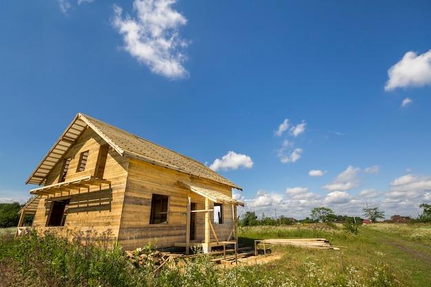 Nuovo cottage tradizionale ecologico di legno dei materiali naturali del legname con il tetto ripido in costruzione in vicinanza verde sullo spazio della copia del cielo blu. concetto di costruzione professionale.