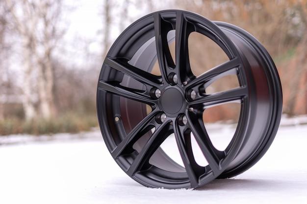 Nuovo elegante cerchi in lega di alluminio spazzolato nero, su neve bianca. inverno. avvicinamento.