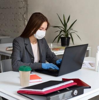 Nuovo normale in ufficio con maschera facciale