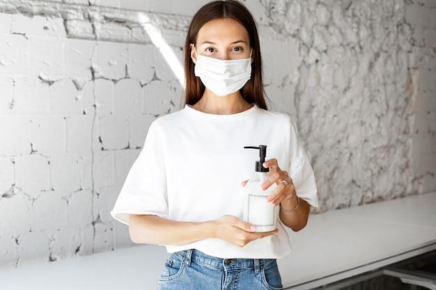 Nuovo normale in ufficio con maschera per il viso e disinfettante