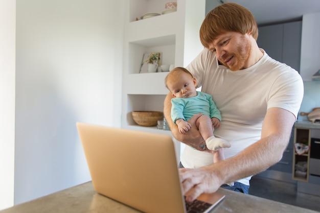 Nuovo papà allegro che resta a casa con il bambino