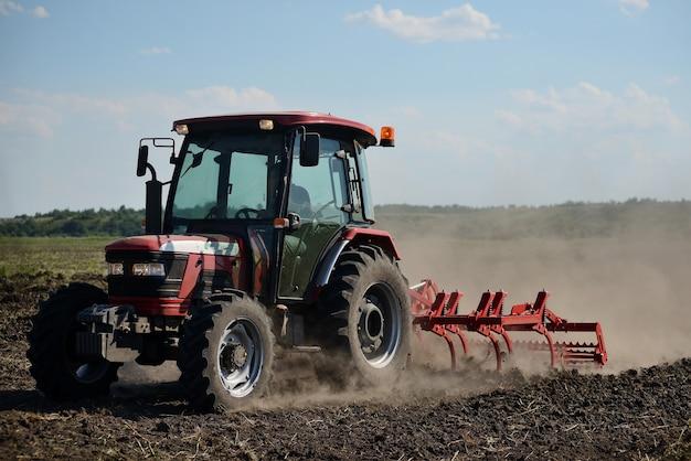 Nuovo trattore rosso sul campo di lavoro. trattore che coltiva il terreno e prepara un campo per la semina
