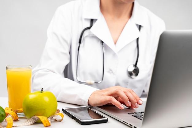 Nutrizionista che per mezzo del suo computer portatile