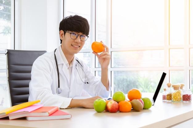Nutrizionista maschio che si siede allo scrittorio della clinica e che tiene frutta arancio fresca con sorridere. concetto di assistenza sanitaria e dieta.