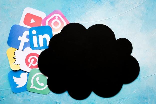 Nuvola di carta nera vicino alle icone dell'applicazione del telefono cellulare sopra fondo blu