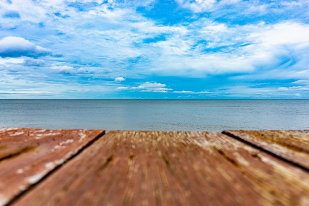 Nuvoloso cielo blu e mare con tavole di legno