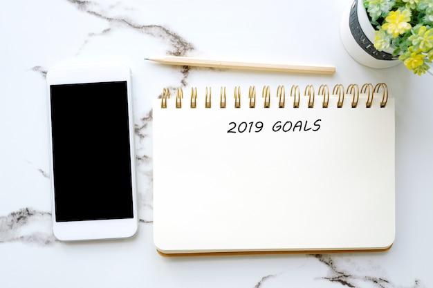 Obiettivi 2019 su carta per appunti e sullo smart phone in bianco con lo schermo in bianco su fondo bianco
