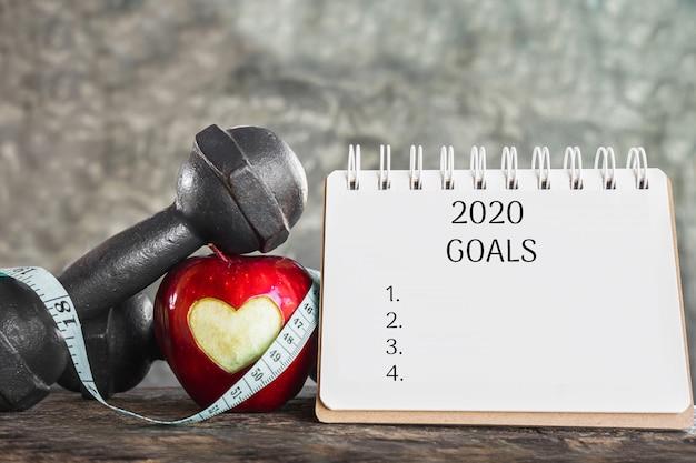 Obiettivi 2020 per il concetto di sport con mela rossa, manubri
