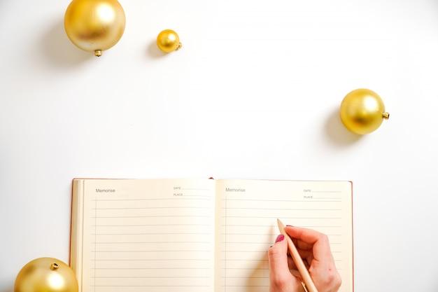 Obiettivi astuti di vita di progettazione della palla dorata di risoluzione del nuovo anno della mano del blocco note del fondo bianco