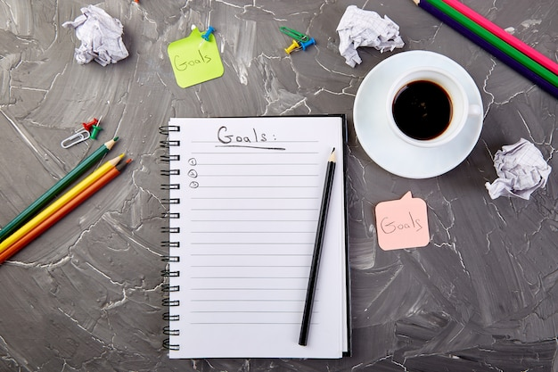 Obiettivi come promemoria su notebook con idea, carta stropicciata, tazza di caffè