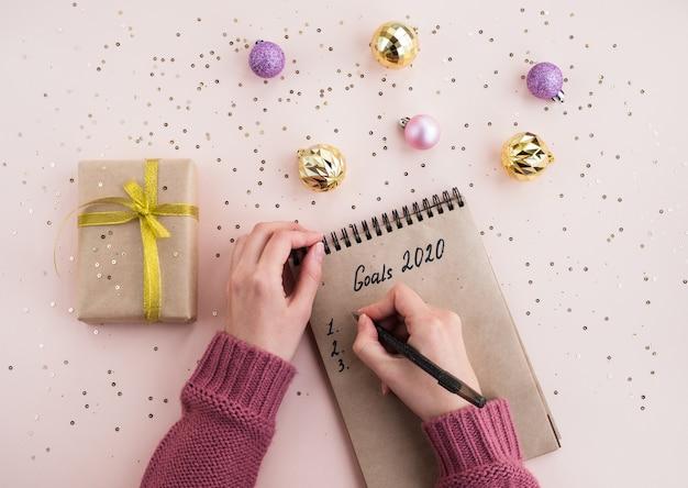 Obiettivi del nuovo anno 2020. la donna scrive i piani in un taccuino su un tavolo. vista dall'alto