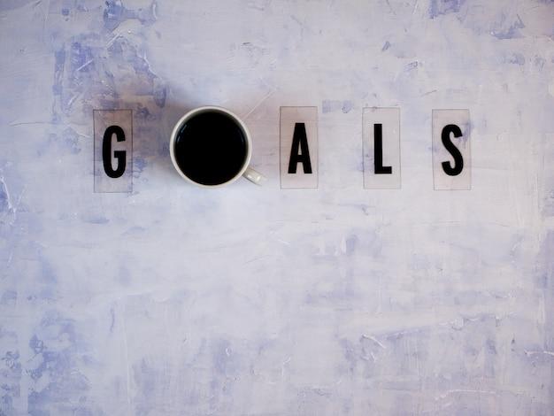 Obiettivi di parola con una tazza di caffè su sfondo chiaro