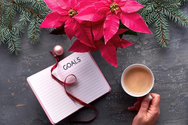 Obiettivi natalizi creativi piatti distesi. mano che regge caffè, notebook con decorazioni natalizie naturali, segnalibro a nastro e ninnolo rosa. ramoscelli rosa vibranti della pianta e dell'abete di stella di natale su fondo scuro.