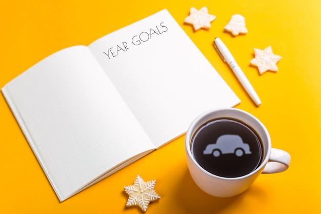 Obiettivi per l'anno scritti in un quaderno su uno sfondo giallo accanto a una tazza di caffè che riflette la forma della macchina