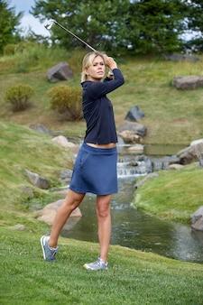 Obiettivo, copyspace. attrezzatura da golf della tenuta di tempo golfing delle donne sul campo verde. la ricerca dell'eccellenza, artigianato personale, sport reale, banner sportivi.