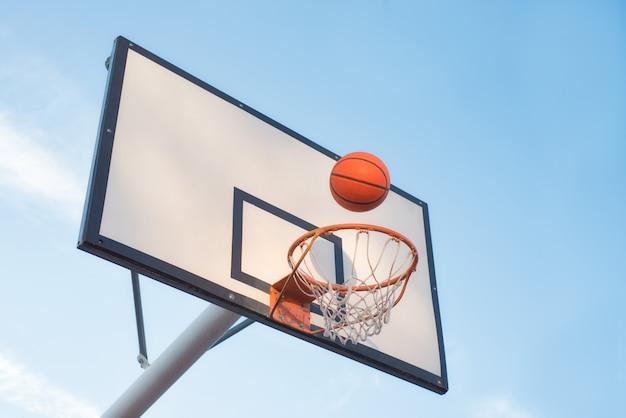 Obiettivo del campo da pallacanestro con la priorità bassa del cielo blu