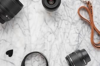 Obiettivo della fotocamera professionale; anelli di prolunga con cuori e cintura sul pavimento di marmo