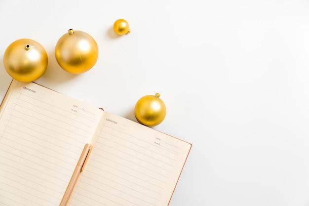 Obiettivo di vita di pianificazione della palla dorata di risoluzione del nuovo anno della scrittura del blocco note del fondo bianco 2019 2020