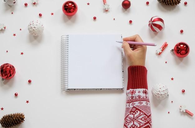 Obiettivo per l'anno nuovo. decorazioni e taccuino di festa con il taccuino pulito sulla tavola bianca