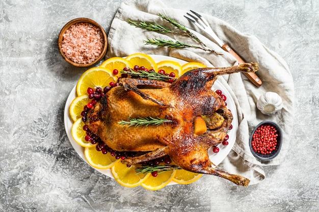 Oca al forno ripiena di arance e rosmarina. tavolo festivo sfondo grigio. vista dall'alto