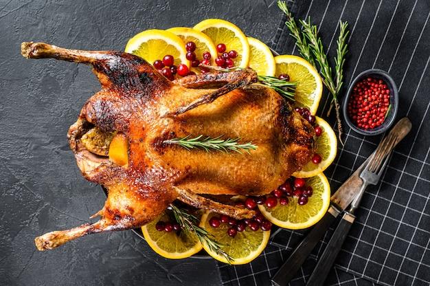 Oca al forno ripiena di arance e rosmarina. tavolo festivo vista dall'alto.