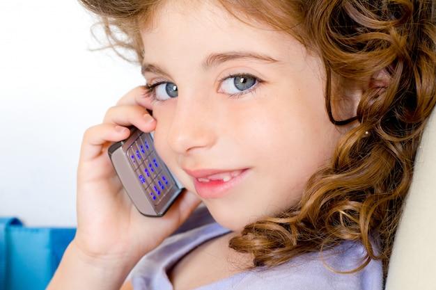 Occhi blu bambino ragazza parlando di telefonia mobile