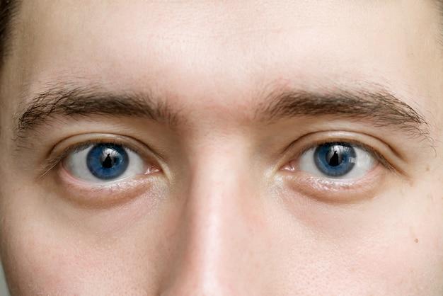 Occhi blu di un uomo da vicino. il concetto di ottica e medicina oftalmologica. lo sguardo maschile