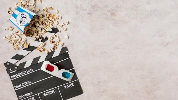 Occhiali 3d con popcorn e ciak su sfondo concreto