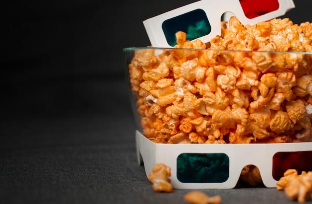 Occhiali 3d e popcorn di formaggio si trovano in una lastra di vetro su un letto grigio