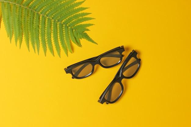 Occhiali 3d, foglia di felce su uno sfondo giallo. vista dall'alto, minimalismo