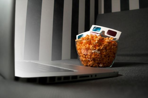 Occhiali 3d, popcorn e un computer portatile sono sdraiati sul divano nella stanza di notte