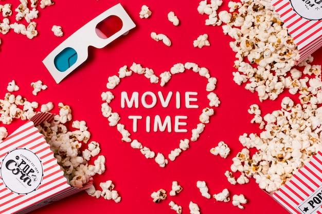 Occhiali 3d; popcorn versato dalla scatola con il testo del film tempo a forma di cuore sul fondale rosso