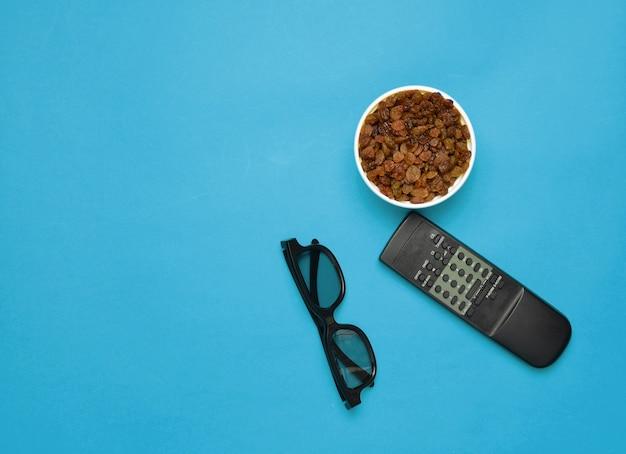 Occhiali 3d, telecomando tv, ciotola con uvetta su sfondo blu
