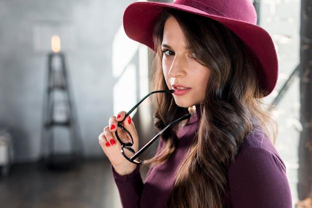 Occhiali alla moda sicuri della tenuta della donna a disposizione che esaminano macchina fotografica