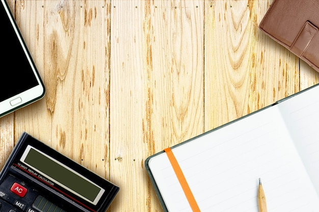 Occhiali, calcolatrice e matita marrone su notebook, vista dall'alto,