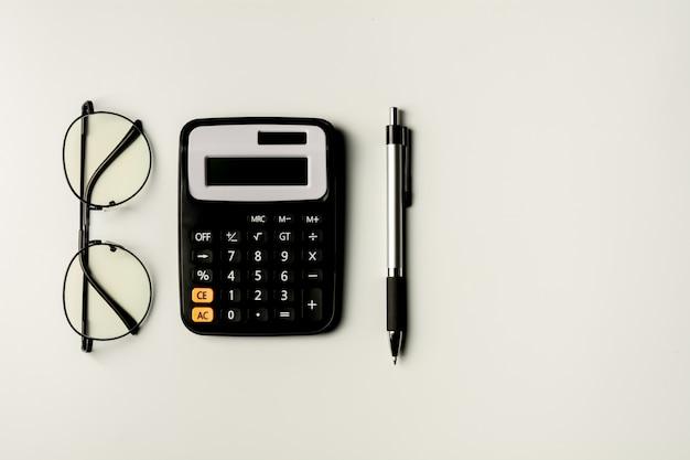 Occhiali, calcolatrice e penna. forniture per ufficio e concetto di educazione.