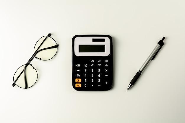 Occhiali, calcolatrice e penna su sfondo bianco