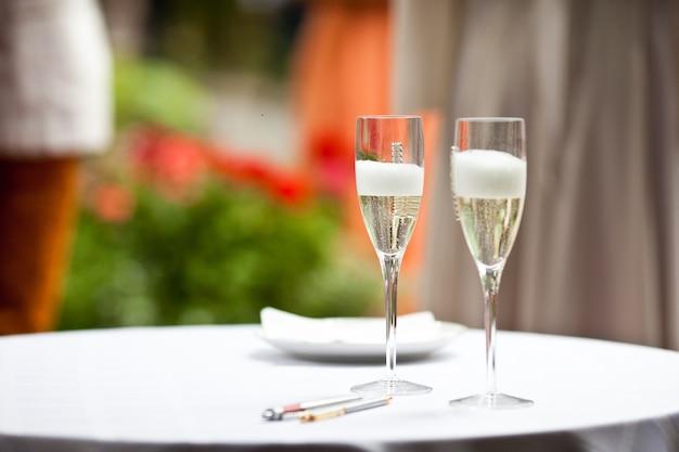 Occhiali con champagne e schiuma stanno sul tavolo bianco