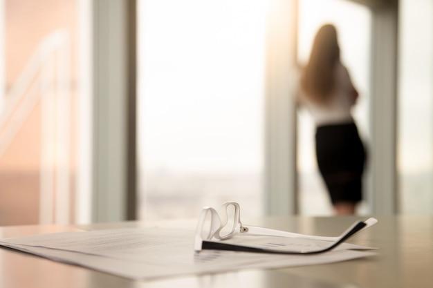 Occhiali correttivi per la lettura sulla scrivania, silhouette femminile in background