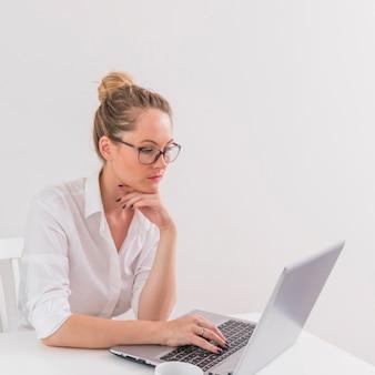 Occhiali d'uso d'uso della giovane donna alla moda che esaminano computer portatile